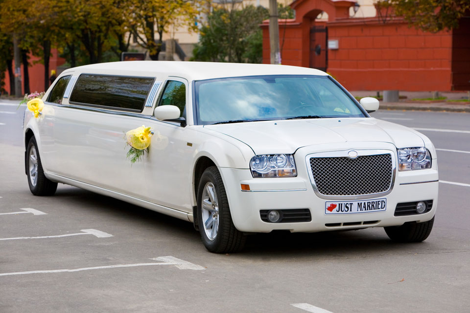 White wedding limousine on the road ornated with flowers